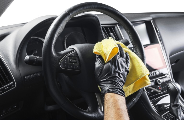 A person wearing a black glove wiping down the steering wheel inside a vehicle with a yellow cloth.