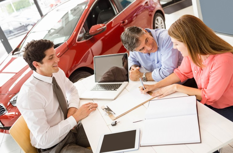 A couple signing important papers at a dealership with an associate.