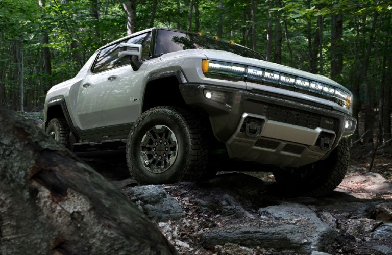 A white 2022 GMC Hummer EV driving off-road in a forest.