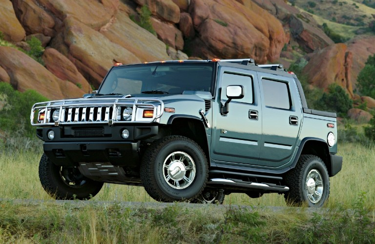 The front and side view of a green 2005 Hummer H2 driving off-road.