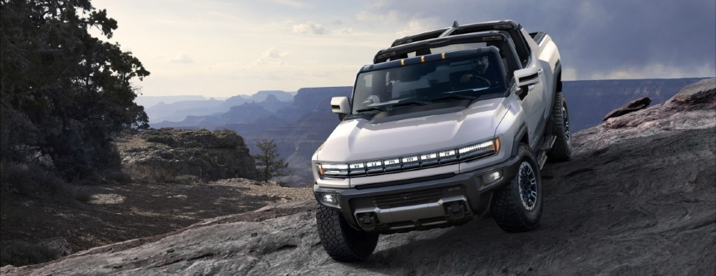 A front view of a white 2022 GMC Hummer EV descending from a large rock face.