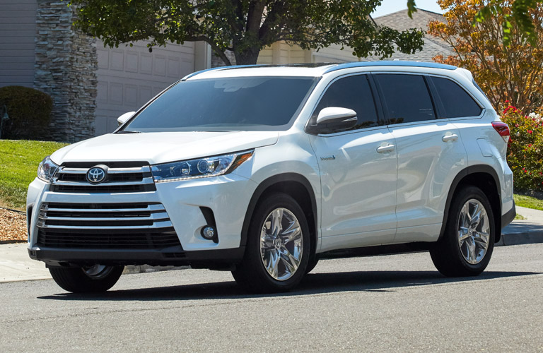 The front and side view of a white 2018 Toyota Highlander Hybrid with all-wheel drive.