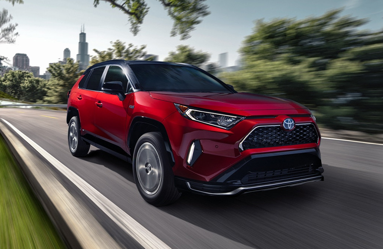 The front and side view of a red 2021 Toyota RAV4 Prime driving away from a city.