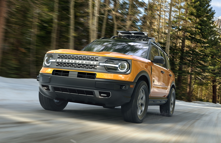 The front side of a yellow 2021 Ford Bronco driving in a forest.