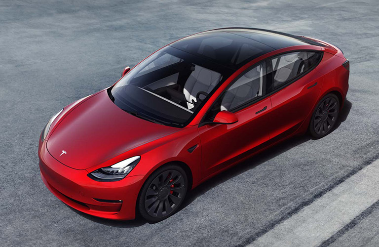 The top and side view of a red 2021 Tesla Model 3.