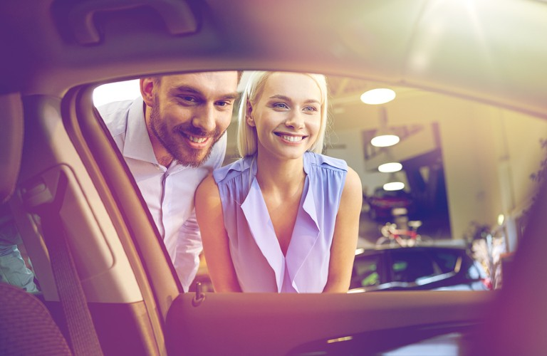 A couple smiling while looking at a vehicle for purchase.
