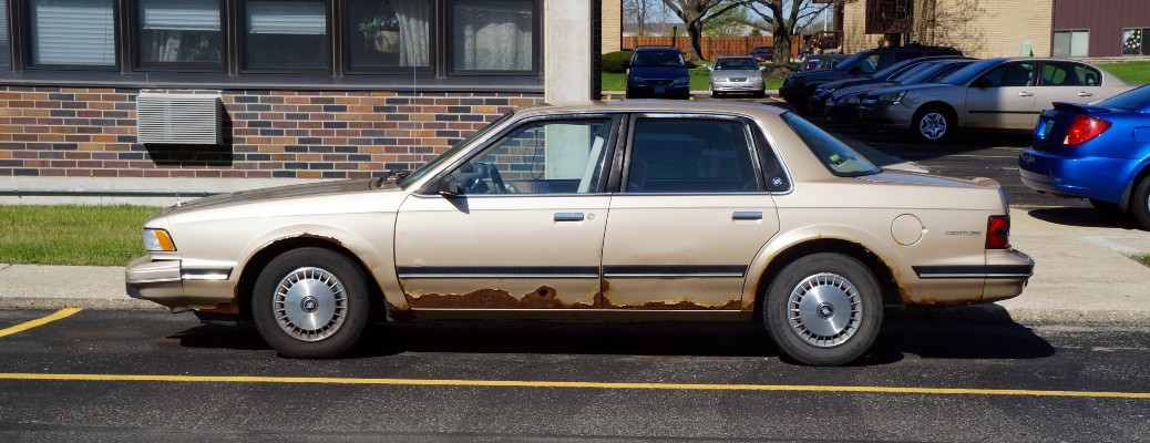The side view of a tan Buick Century with rust along the bottom of the exterior.