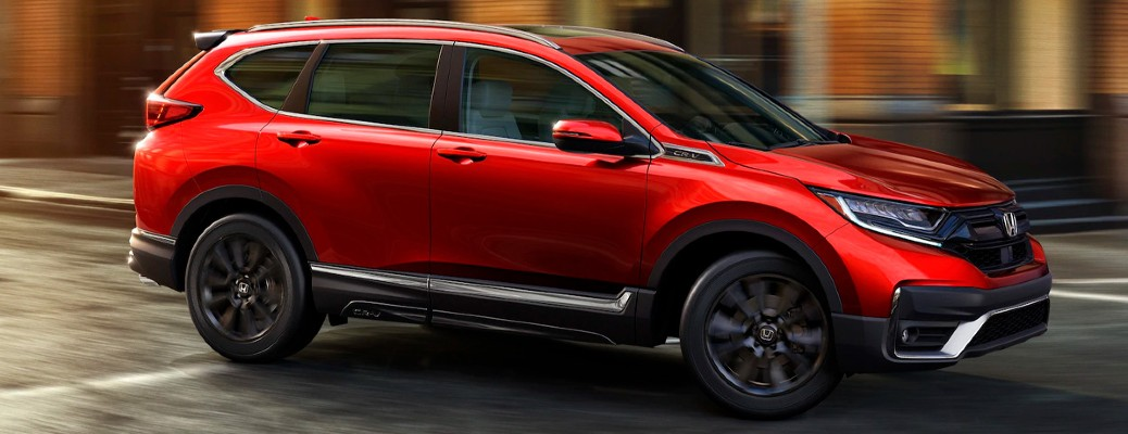 The side view of a red 2021 Honda CR-V driving in a city.