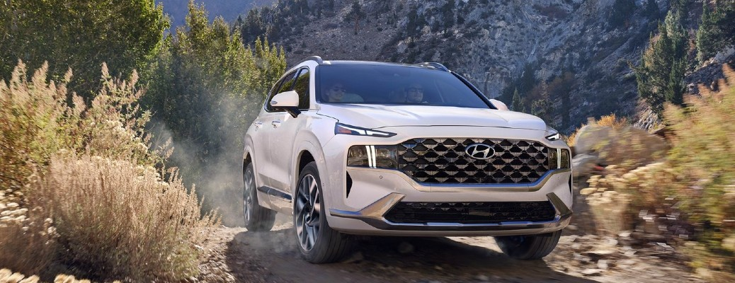 The front side of a white 2021 Hyundai Sante Fe driving off-road.