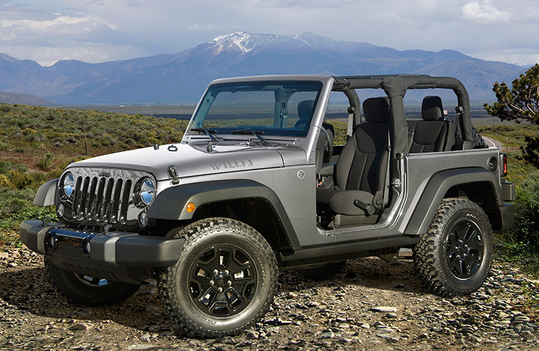 The front and side view of a gray 2017 Jeep Wrangler with its front doors off and soft cover down.