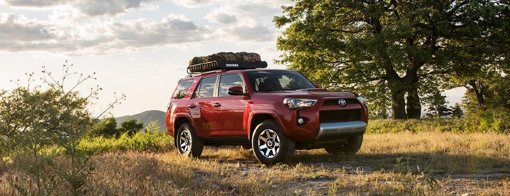 The front and side view of a red 2017 Toyota 4Runner driving off-road.