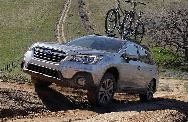 The front and side view of a silver 2019 Subaru Forester driving off-road with a bike rack with bicycles on it.