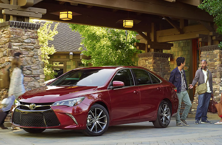 People walking around a red 2016 Toyota Camry.