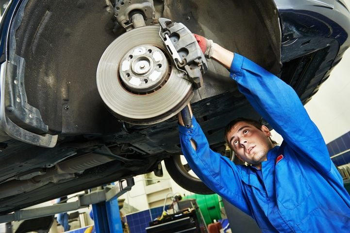 A mechanic working on a brake repair for a customer.