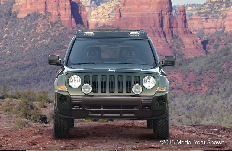 The front side of a dark green 2016 Jeep Patriot.