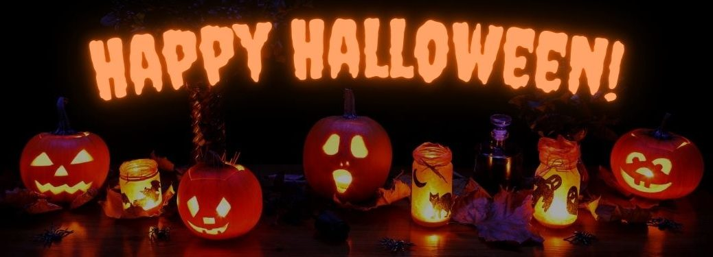 Lit Halloween Jack-o-Lanterns and Candles on a Table with Glowing Orange Happy Halloween Text