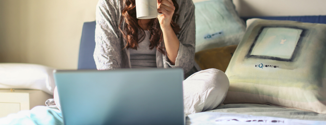Woman using laptop and holding coffee mug