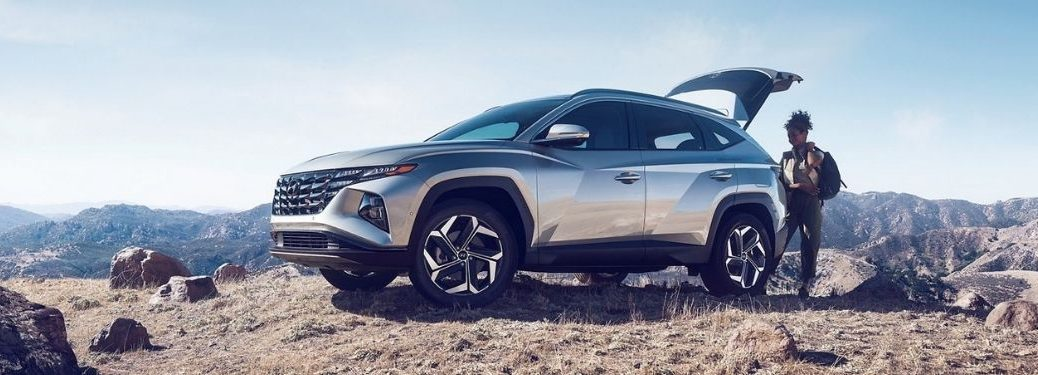 Silver 2022 Hyundai Tucson on a Hill with Woman Putting Cargo in the Back