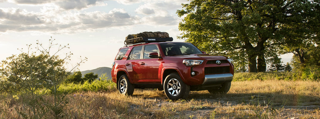 Red 2017 Toyota 4Runner model driving down dirt road and carrying cargo on top