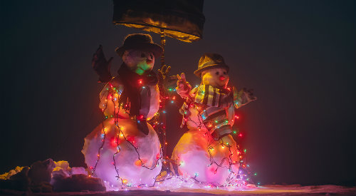 Two snowman figures lit up as part of holiday light show