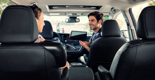 Man and woman inside 2018 Sienna with man operating tablet connected to Internet