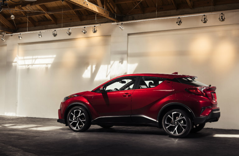 Red 2018 Toyota C-HR model driving in front of closed door panels