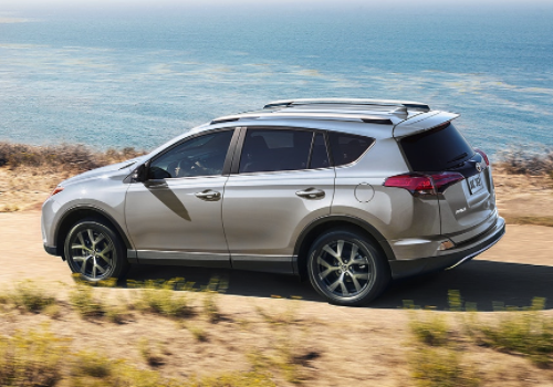 Silver 2018 Toyota RAV4 driving on dirt road in front of body of water