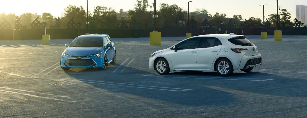 Two 2019 Toyota Corolla Hatchback models parked diagonally to each other at sundown in empty lot