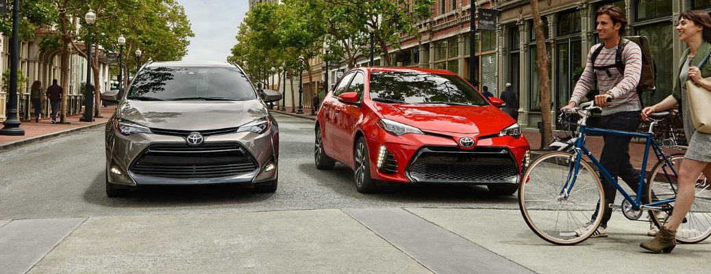 Two Toyota Corolla models parked on street in front of bikers crossing the road