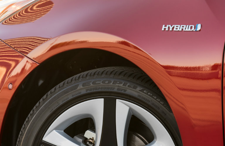 close up of red toyota prius tire and hybrid badge