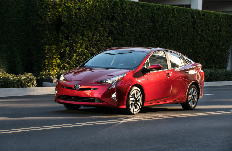 red toyota prius driving on city road