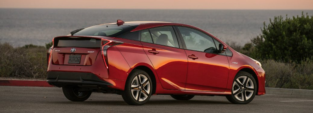 right and rear of red toyota prius near water