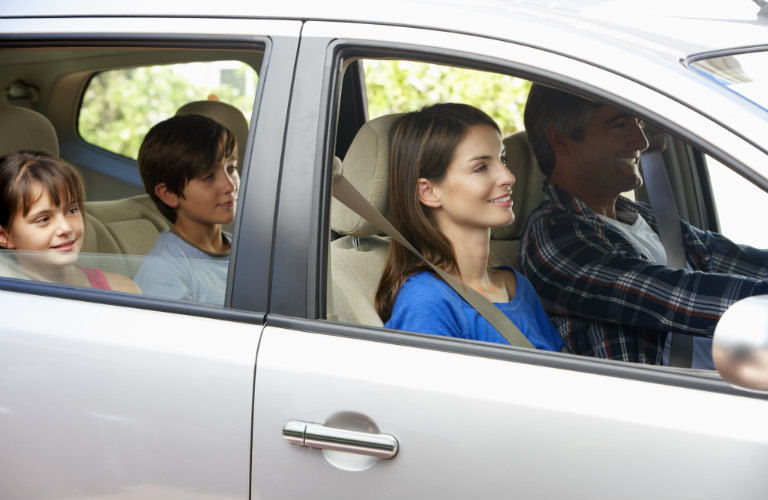 happy family sitting in silver car