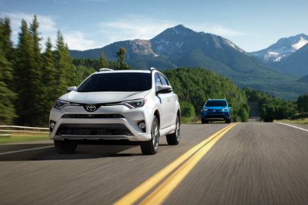 Two 2018 Toyota RAV4s driving down a hilly road