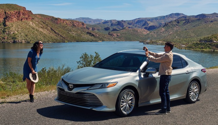 A man takes a photo of a woman near a 2019 Toyota Camry