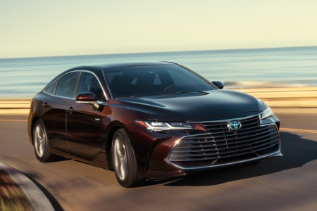 2019 Toyota Avalon driving down a road by the water