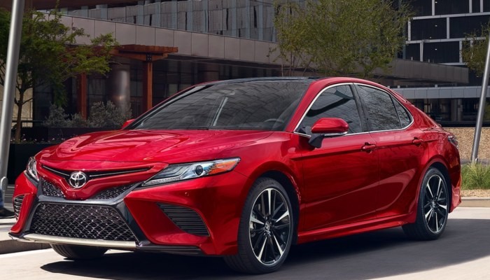 A red 2019 Toyota Camry parked in front of a building