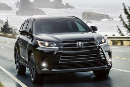 2019 Toyota Highlander driving down a road by the shore