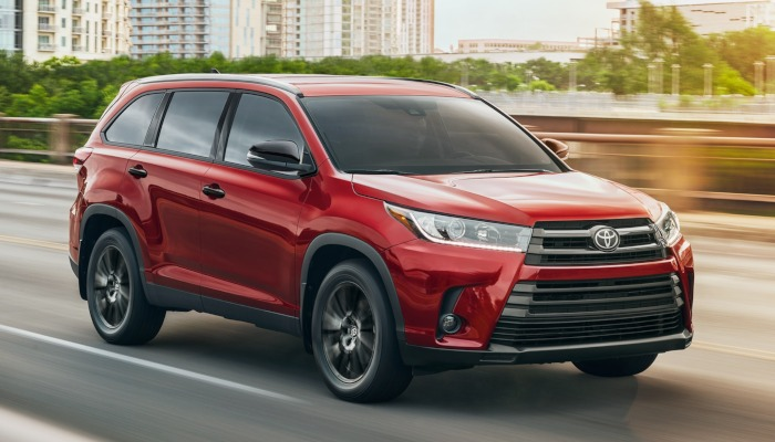 2019 Toyota Highlander driving out of a city on a highway
