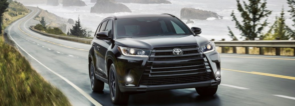 2019 Toyota Highlander driving down an oceanside road on a cloudy day