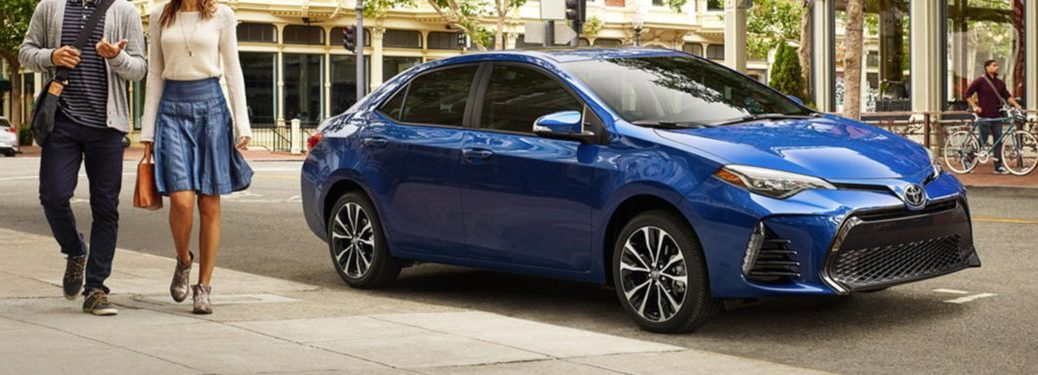 A couple walking next to a parked 2019 Toyota Corolla