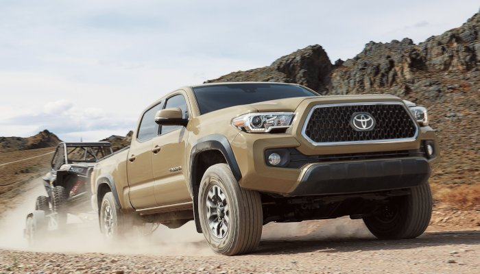 2019 Toyota Tacoma towing a smaller vehicle in the desert