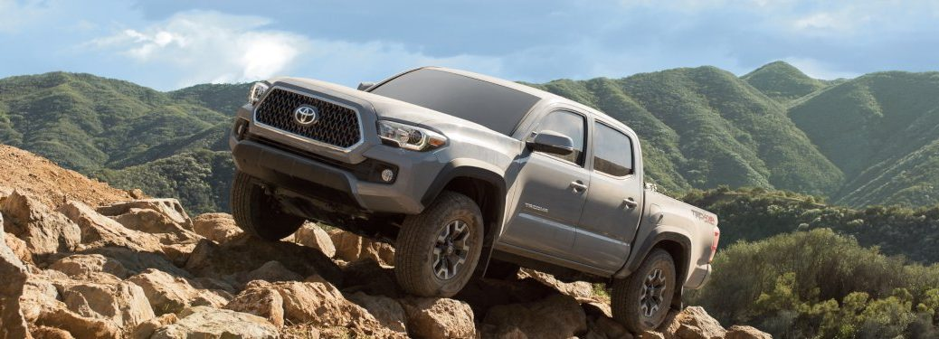 2019 Toyota Tacoma driving up a rocky hill