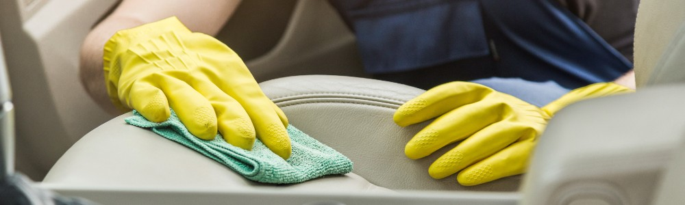 someone cleaning car seat with yellow gloves