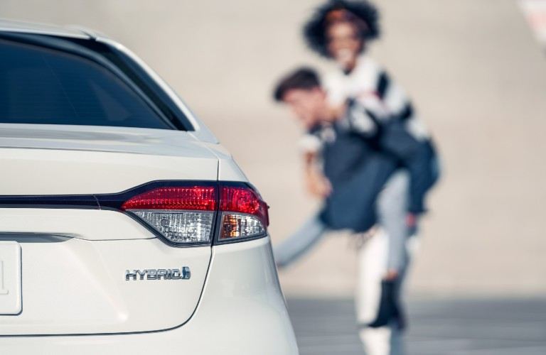 2021 Toyota Corolla hybrid with couple in the background