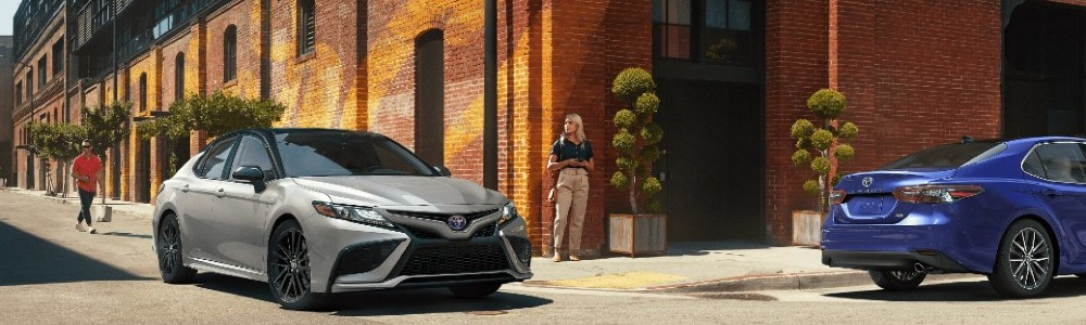 two 2021 Toyota Camry models turning corner in city