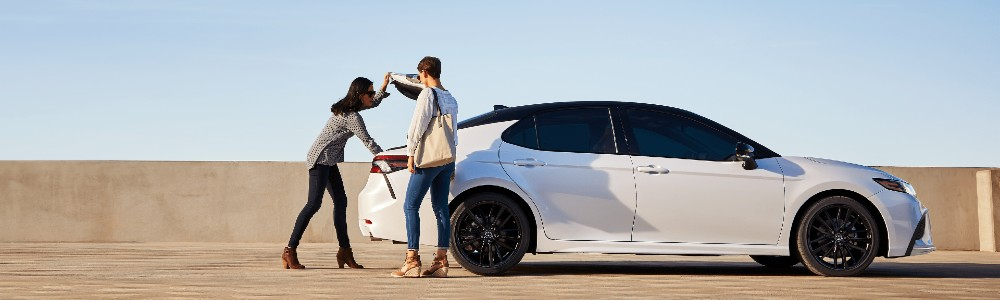 couple near the truck of the 2021 Toyota Camry TRD