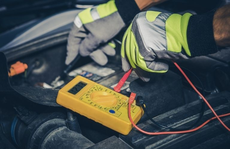 Image of an auto mechanic tending to a car battery