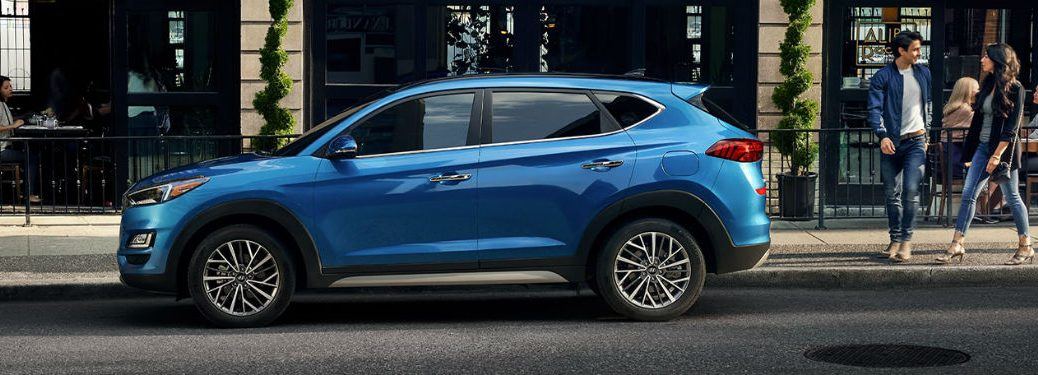 2020 Hyundai Tucson blue exterior driver side parked on side of street people behind vehicle