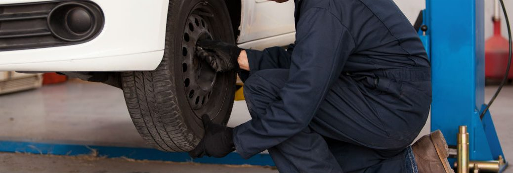 Mechanic Rotating Tires in a Service Department